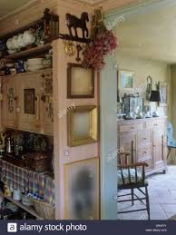 pink cabinet in country kitchen with dried flowers and picture