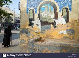 fes el bali morocco north africa an old man walks past a mural fes el bali morocco north africa an old man walks past a mural wall painting of the blue gate or bab boujeloud