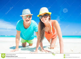 Tropical Clothes For Travel Couple In Bright Clothes And Hats Sitting At Sandy Tropical Beach