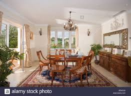 chandelier above traditional table and chairs in spanish country