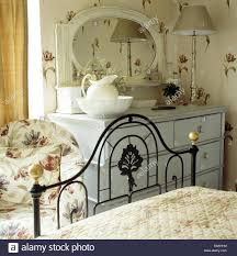 ornate black wrought iron bed in cottage bedroom with tulip