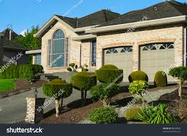 luxury bungalow house garage ornamental landscaping stock photo