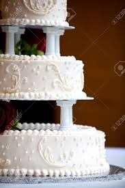 a white wedding cake with three levels and red roses stock photo