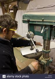 self building house joiner in workshop at pillar drill making