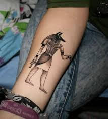 small black and white anubis god on forearm
