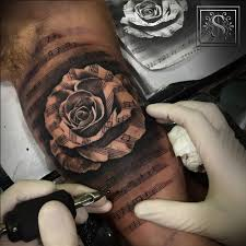 black and grey style music staff rose tattoo artist sergio