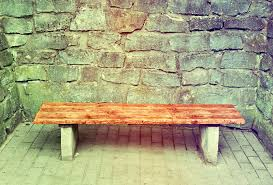 wooden garden bench at medieval brick wall stock photo image