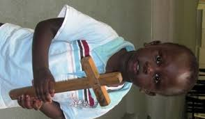 sudanese boy holding a cross at catch the ministries
