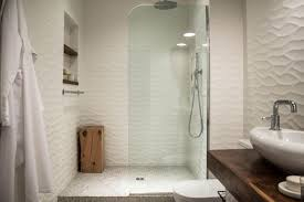 walk in shower with rippled tile walls and glass wall undulating