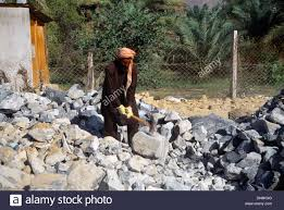 hammer town dubai uae hatta old town man breaking up rocks using sledge hammer