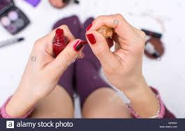 applying nail polish in bed point of view stock photo