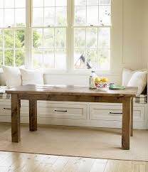 create a cozy dining nook by placing a reclaimed farm table in