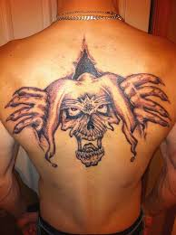 grey ink evil jester face and tribal design tattoo on upper back