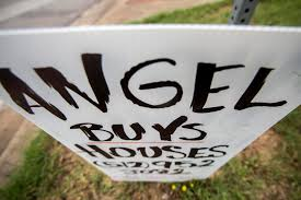 what s up with those handmade we buy houses signs around