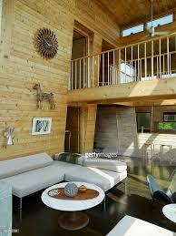 double height open plan living room with mezzanine walkway in wood