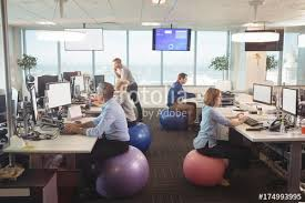 Sitting On A Medicine Ball At Desk Thoughtful Businesswoman Sitting On Exercise Ball At Office