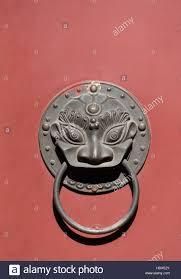 chinese door knocker on red door in a beijing hutong china stock