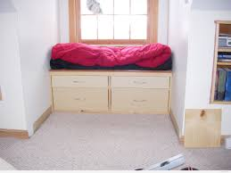 cream wooden bay windows with drawers having pink and black pad on