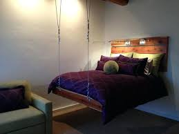 a pair of hanging bed in rustic enclosed porch with wooden frame