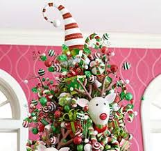 pier 1 pink present décor tops a tree with assorted ornaments in