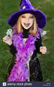 little beautiful with halloween witch costume eating candy