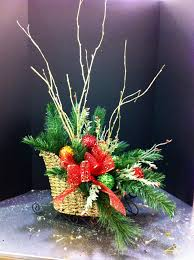 small wicker sleigh with greens and multi colored ornaments