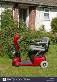 three wheel electric wheel chair parked on lawn outside small