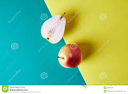 two whole fresh pear fruit cut in half view from above on green