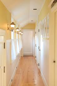 hallway with yellow wall colors and wall sconces hallway