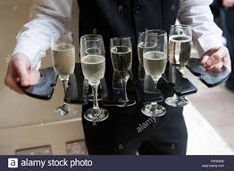 a waiter holding a tray of full champagne glasses at a luxury