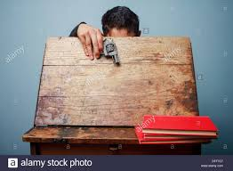 Picture Of Student Sitting At Desk by Student Sitting At Old School Desk Holding A Gun There U0027s A Stack