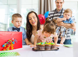 family watching blowing out candles on birthday cake at home