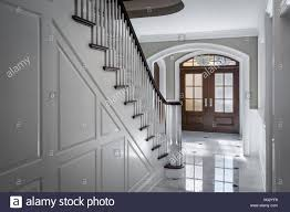 white foyer interior staircase front door luxurious house stock