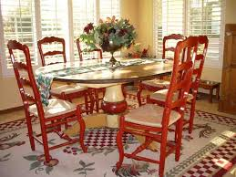 painted red vintage wooden chairs and oval kitchen table in a