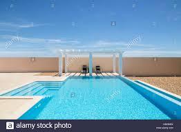white poolside pergola gazebo next to an infinity pool swimming