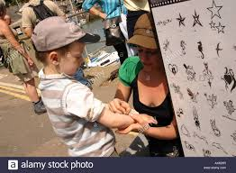 young child having a henna tattoo applied at the sea side