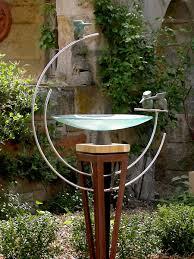 glass dish birdbath with three bronze kingfishers in a double loop
