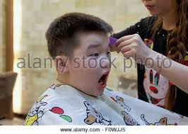 7 year old boys hair cuts boy getting a buzz hair cut by his father stock photo 114709239