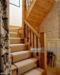 wooden staircase with cream carpet and cream wallpaper in the