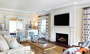 television mounted just above the mantle this mantle is gorgeous white wood that encases a large fireplace it moves upwards to