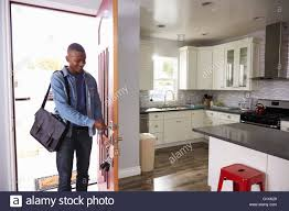 man coming home from work and opening door of apartment stock