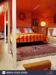 striped cushions and orange duvet on metal bed in modern red loft