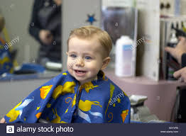 one year old boy sits in barber stool for first haircut model