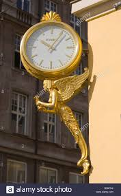 gilt angle holding a hourglass supporting a clock shop sign of