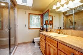 bright bathroom with mocha tile floor wood storage cabinet and