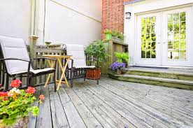 wooden deck on house with chairs and french doors stock photo