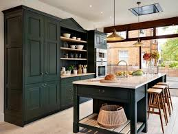 large english kitchen with white cabinetry and ceramic backsplash dark green kitchen storage with a big island and dining space in a wonderful english kitchen