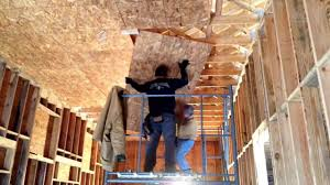hanging osb plywood on a high ceiling a scaffold and two people