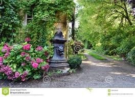 water fountain on the backyard with flowers stock photo image