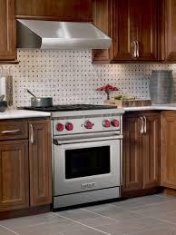 kitchen with a wolf range a custom hood black subway tile backsplash